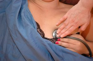 Stethoscope placed at the fifth intercostal space at the left mid-clavicular line with client repositioning breast tissue