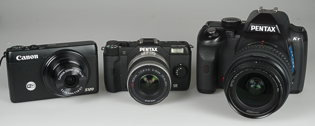 Three cameras. Left to right. Canon point-and-shoot, Penax mirrorless, and Pentax K-r DSLR.